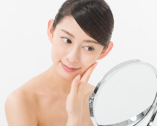 鏡で顔を見る日本人美人女性