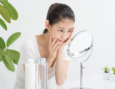 心配そうに鏡で顔を見る日本人美人女性