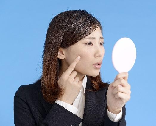 心配そうにほほに指をあてる日本人女性